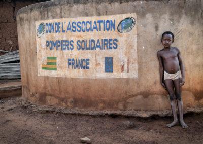 Petit garçon togolais devant des latrines construites par pompiers solidaires dans son village de Notse