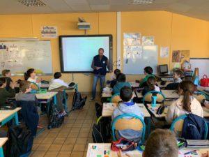 un membre de Pompiers Solidaires présentent les actions de l'association devant une salle de classe