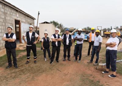 Bénévoles de Pompiers Solidaires entourés des membres du village où un puits va être construite