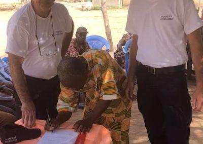 Deux membres de Pompiers Solidaires signent une cinvention de partenariat avec un chef de village