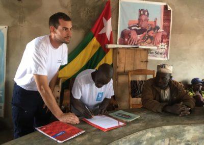 Un membre de Pompiers Solidaires signe une cinvention de partenariat avec un chef de village