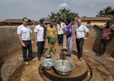 Trois bénévoles de Pompiers Solidaires et deux membres d'un village du Togo autour d'un puits finalisé