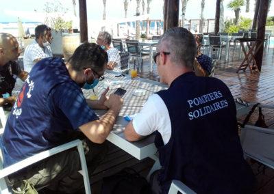 un volontaire de Pompiers Solidaires assis à table avec un libanais en train de travailler